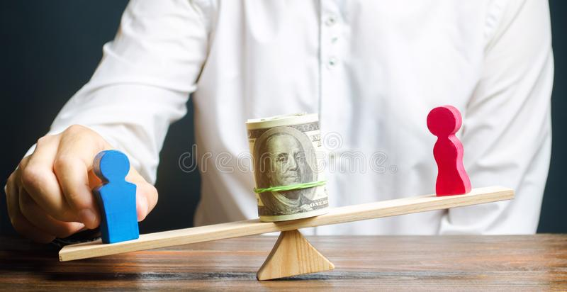 Wooden figures of man and women on the scales. Concept of gender pay gap. Income inequality. Oppression of women. Gender. Discrimination. Underestimation of royalty free stock photo