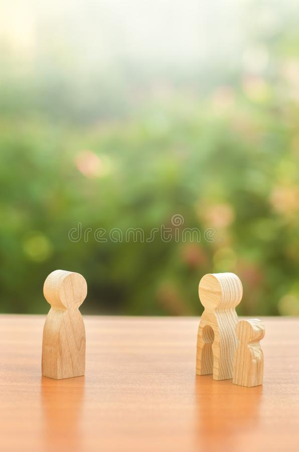 Wooden figures of a mother with a child stands apart from the father. Deprivation of parental rights. The child stay with the mother. Conflict resolution in stock image