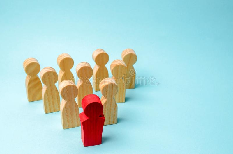 Wooden figures of people. The boss of the business team indicates the direction of movement to the goal. The crowd is following. The leader. The concept of stock photos