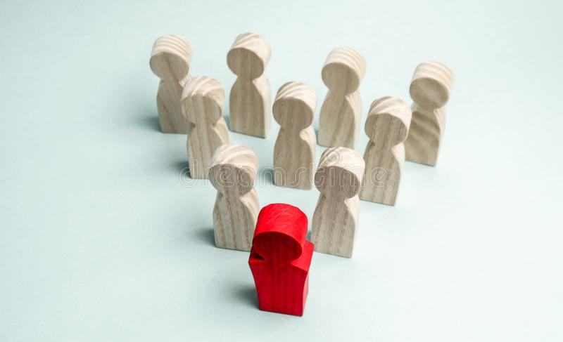 Wooden figures of people. The boss of the business team indicates the direction of movement to the goal. The crowd is following. The leader. The concept of stock photography