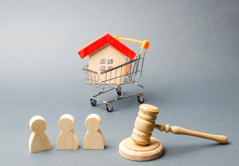 Wooden figures of people, a house in a supermarket trolley and a judge`s hammer. Auction. Public sale of real estate. royalty free stock photo