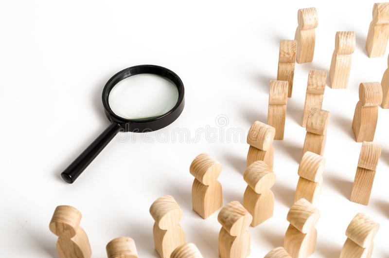 Wooden figures of people look at the magnifying glass. Search for answers to questions, searches for home or work. Problem solving. And tasks, self-organization royalty free stock image