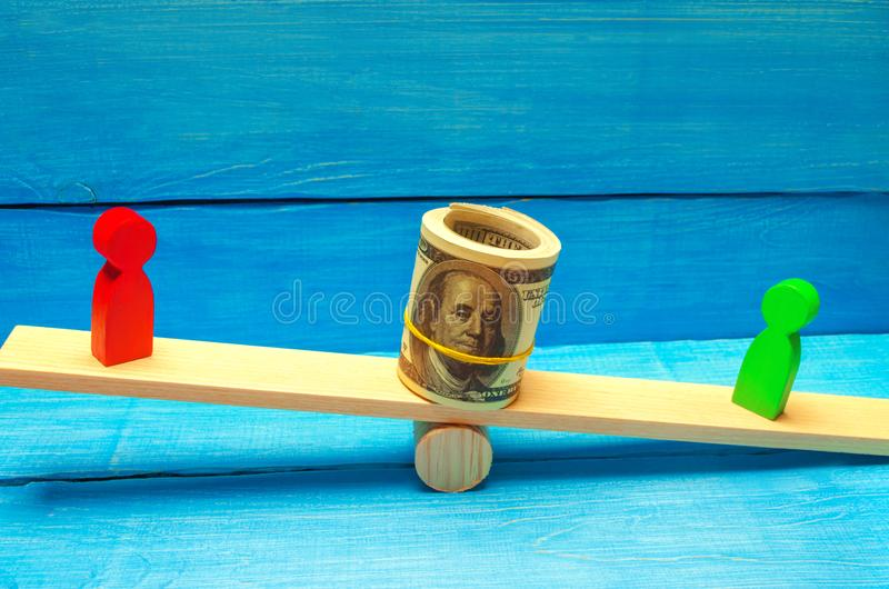 Wooden figures of people on scales and dollars between them. a dispute between two businessmen. trial. debt restructuring. wage ar. Rears. protection of employee royalty free stock photo