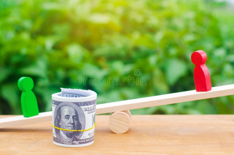Wooden figures of people on scales and dollars between them. a dispute between two businessmen. trial. debt restructuring. wage ar. Rears. protection of employee royalty free stock image