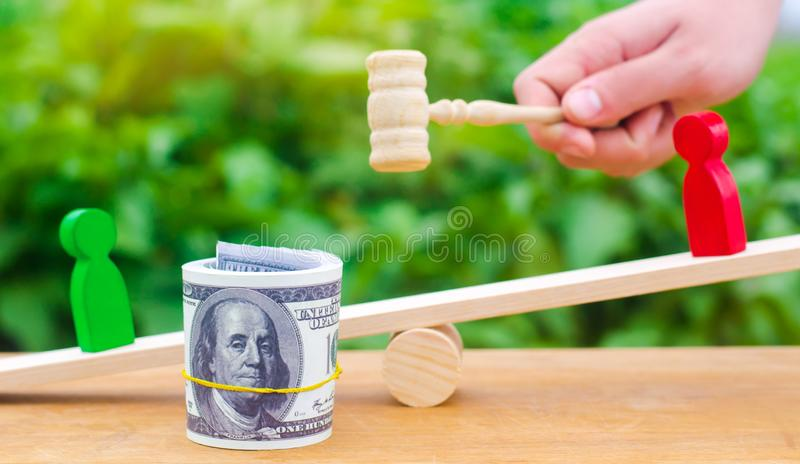 Wooden figures of people on scales and dollars between them. a dispute between two businessmen. trial. debt restructuring. wage ar. Rears. protection of employee royalty free stock images