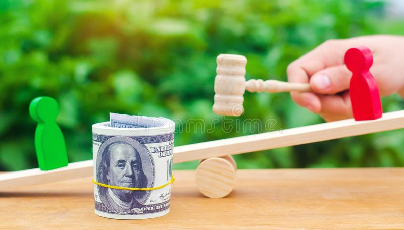 Wooden figures of people on scales and dollars between them. a dispute between two businessmen. trial. debt restructuring. wage ar. Rears. protection of employee royalty free stock photography