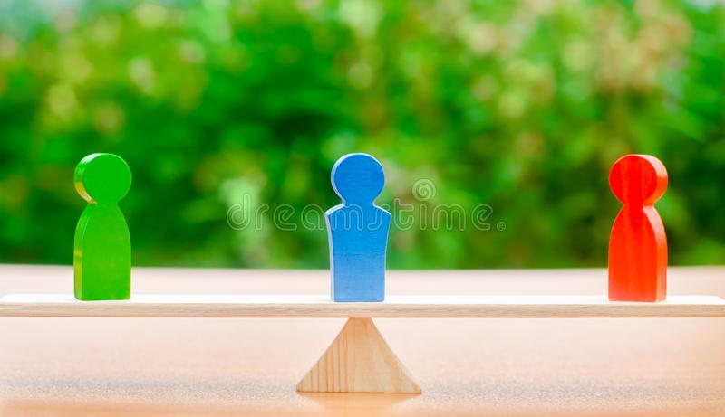 Wooden figures of people on scales and a mediator / arbitrator. Conflict of interest. Resolving conflict situations. Conclusions royalty free stock photo
