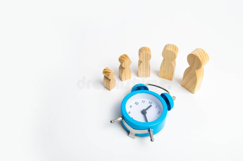 Wooden figures of people from small to large stand around the blue alarm clock. The concept of self-development, growth of persona royalty free stock photos
