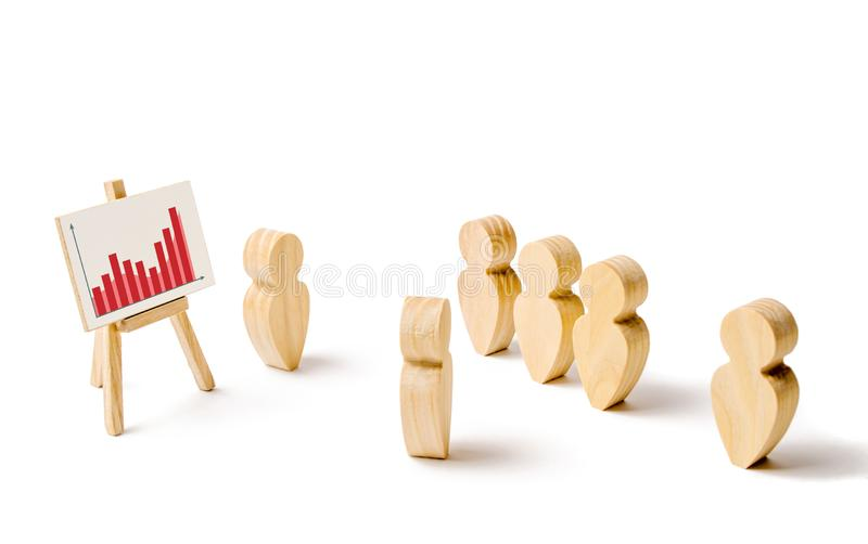 Wooden figures of people stand in the formation and listen to their leader. Business training, briefing and inspirational speech. stock photography
