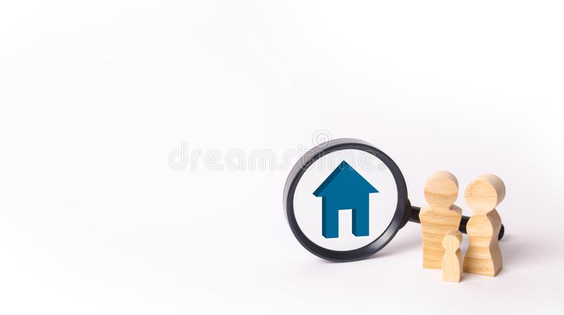 Wooden figures of people stand near the magnifying glass. The fa. Mily is looking for something. The concept of housing search. Marketing, management. Human stock photo