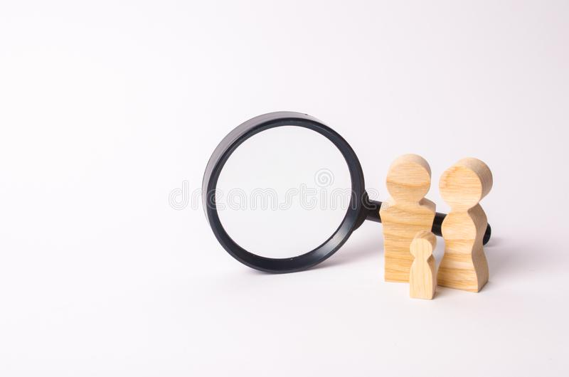 Wooden figures of people stand near the magnifying glass. The family is looking for something. The concept of housing search. royalty free stock photography