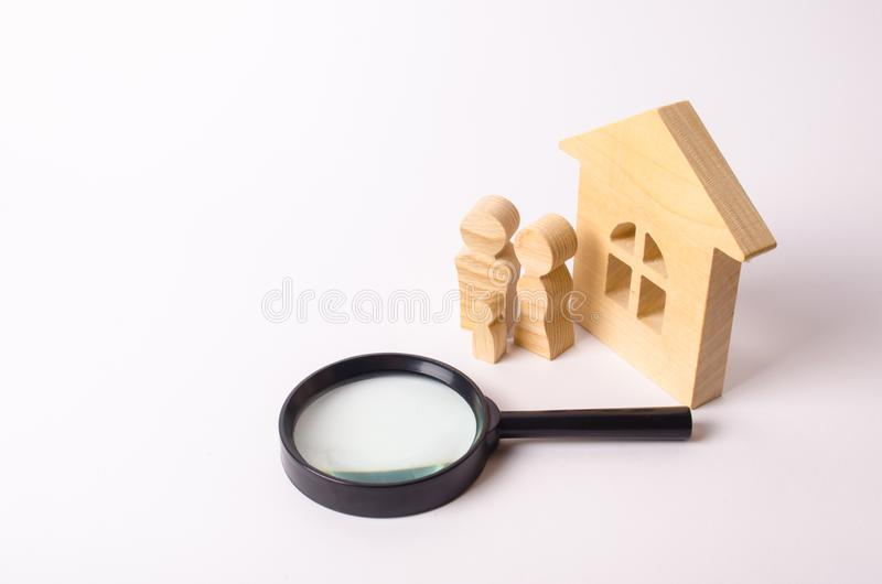 Wooden figures of people are standing near a wooden house and a magnifying glass. The concept of home search, buying and selling. royalty free stock photos