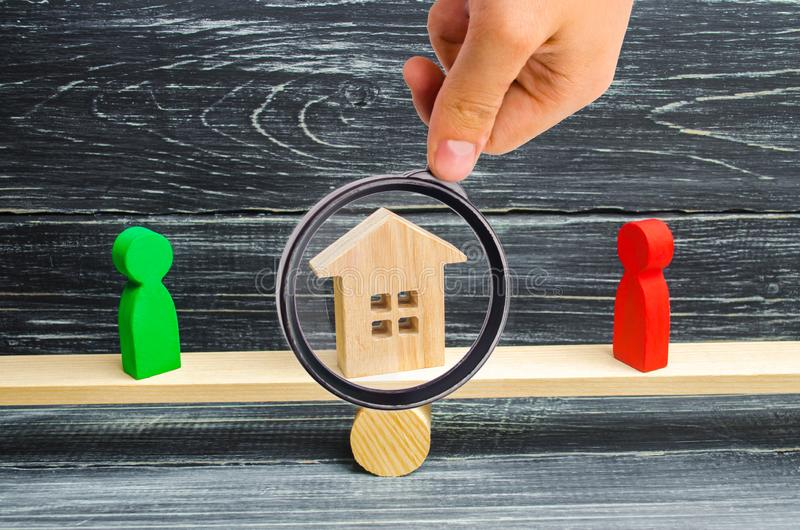 Wooden figures on the scales. clarification of ownership of the. House, real estate. court. rivals in business. competition. concept of success and power royalty free stock photo