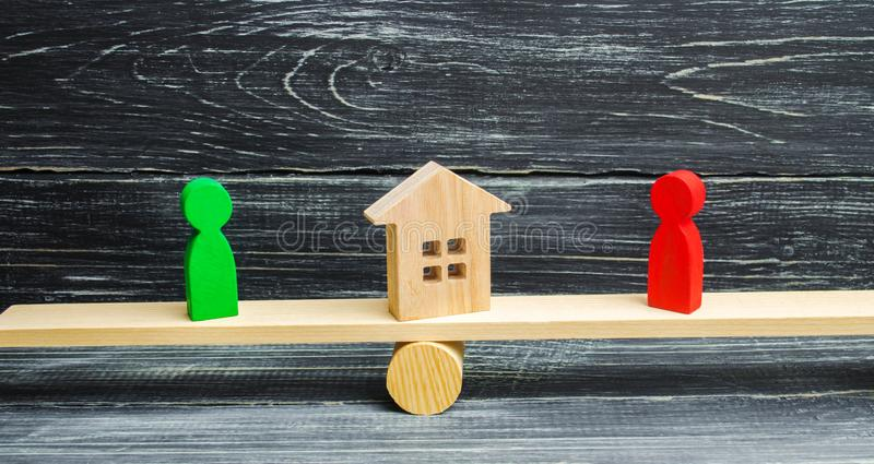 Wooden figures on the scales. clarification of ownership of the house, real estate. court. rivals in business. competition. victor. Y and defeat. concept of stock photography