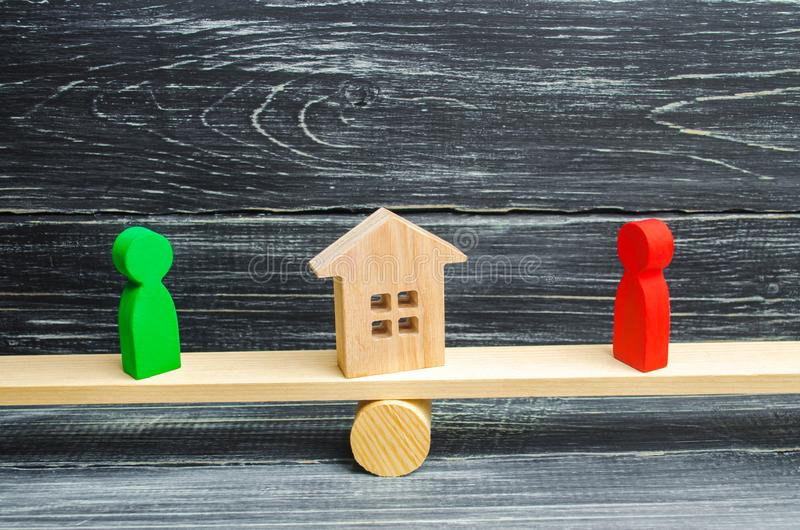 Wooden figures on the scales. clarification of ownership of the house, real estate. court. rivals in business. competition. victor. Y and defeat. concept of royalty free stock images