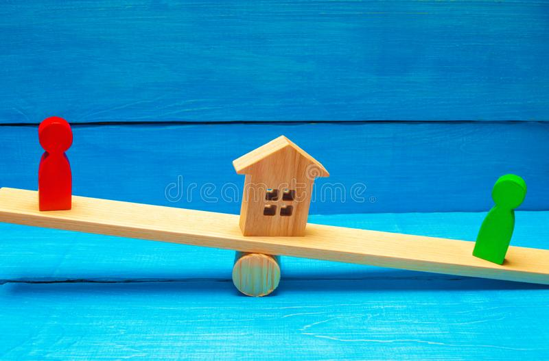 Wooden figures on the scales. clarification of ownership of the house and real estate / property. rivals in business competition. royalty free stock photography
