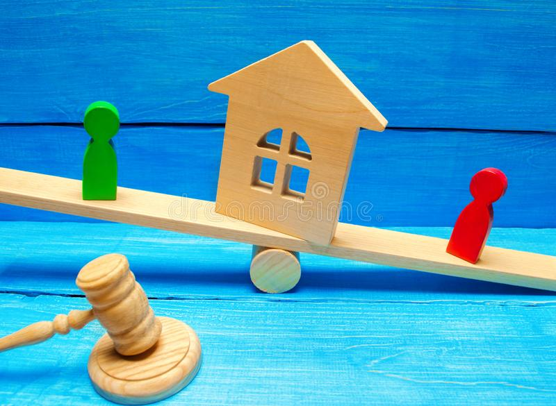 Wooden figures on the scales. clarification of ownership of the house and real estate / property. rivals in business competition. royalty free stock image