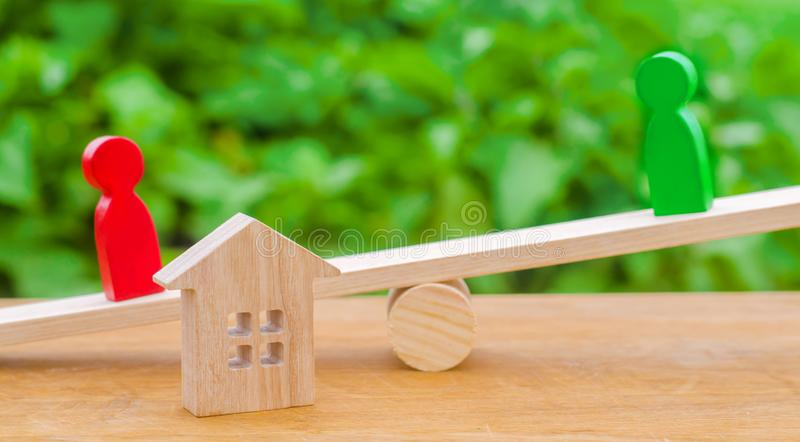 Wooden figures on the scales. clarification of ownership of the house, real estate. rivals in business. competition, court. Estate. Law concept. divorce and stock photography