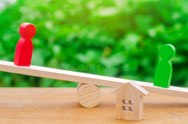 Wooden figures on the scales. clarification of ownership of the. House, real estate. rivals in business. competition, court. Estate law concept. divorce and stock photos