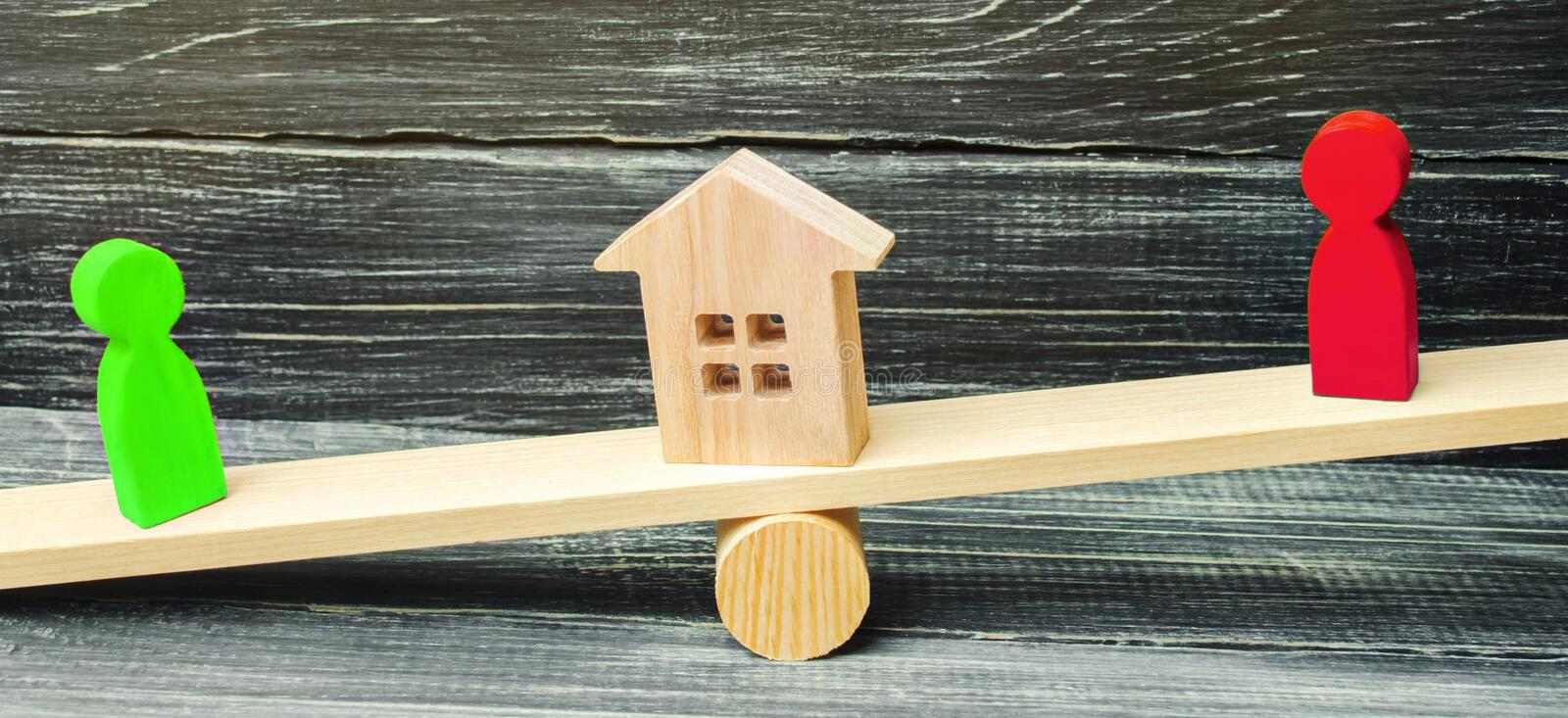 Wooden figures on the scales. clarification of ownership of the royalty free stock photos