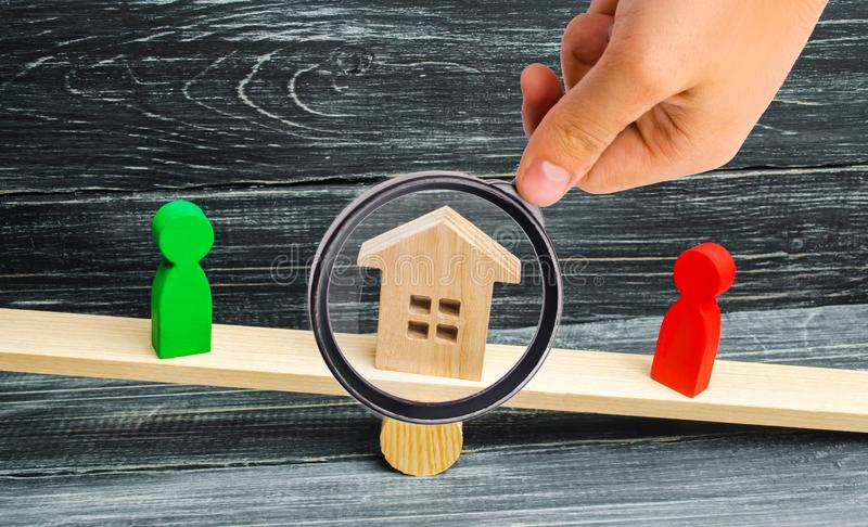 Wooden figures on the scales. clarification of ownership of the. House, real estate. court. rivals in business. competition. victory and defeat. concept of royalty free stock photos