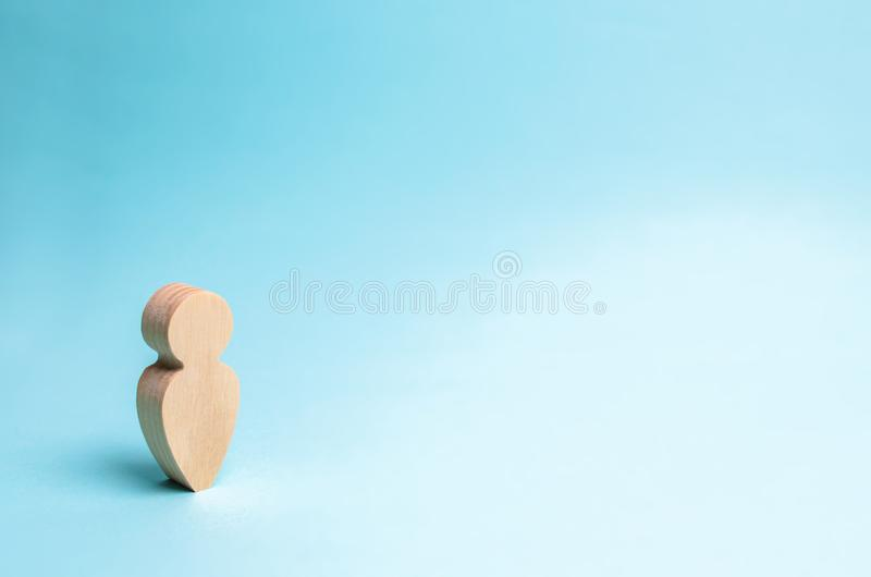 Wooden figurine of a man on a blue background. A lonely man, minimalism. royalty free stock image