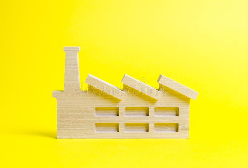 Wooden figurine of a plant or factory on a yellow background. The concept of industry and production. Recycling raw materials. stock images
