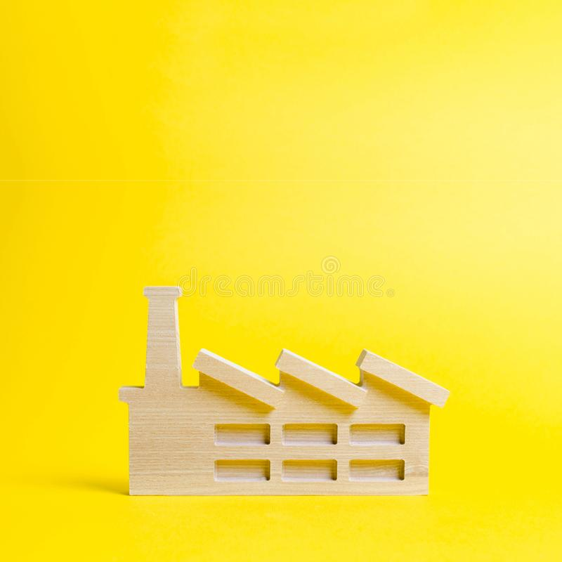 Wooden figurine of a plant or factory on a yellow background. Recycling raw materials. The concept of industry and production. stock photo