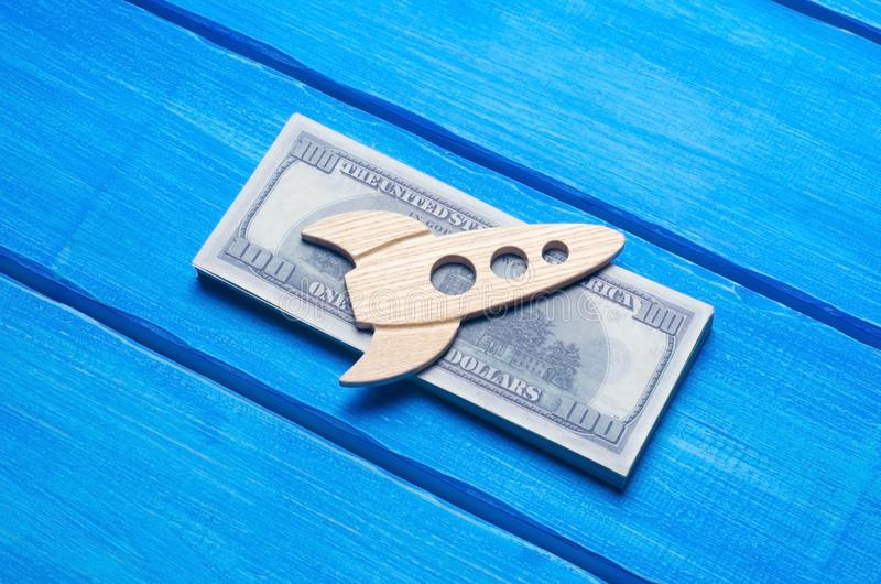 A wooden figurine of a rocket on a pack of dollars, on a blue background. The concept of investment, rapid investment growth. royalty free stock photography