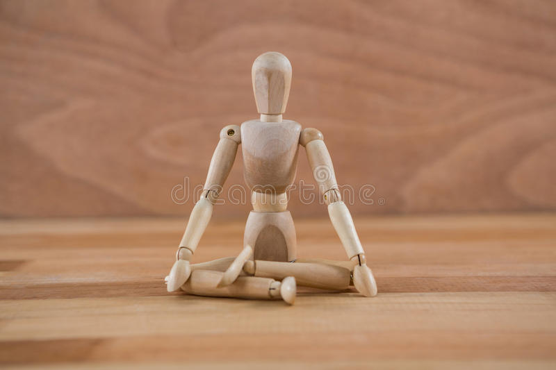 Wooden figurine sitting in a lotus position. On wooden floor royalty free stock photography