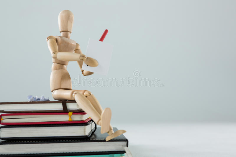 Wooden figurine sitting on a pile of books writing on a paper royalty free stock photo