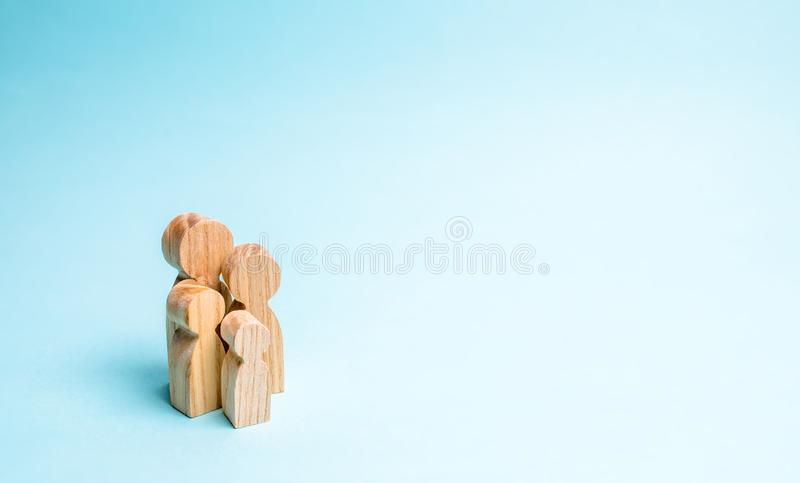 Wooden figurines of the family stand on a blue background. The concept of a classic traditional family. values, unity, loyalty, stock images