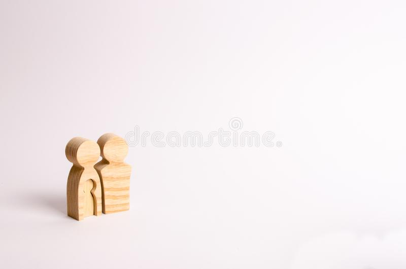 Wooden figurines of parents stand on a white background. Concept of pregnancy, young family. Planning for the family royalty free stock photo