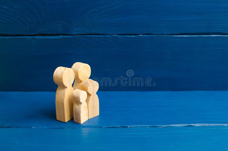 Wooden figurines of people in the shape of a family on a blue background. The concept of family values, family continuation. And family planning. Caring for royalty free stock photography