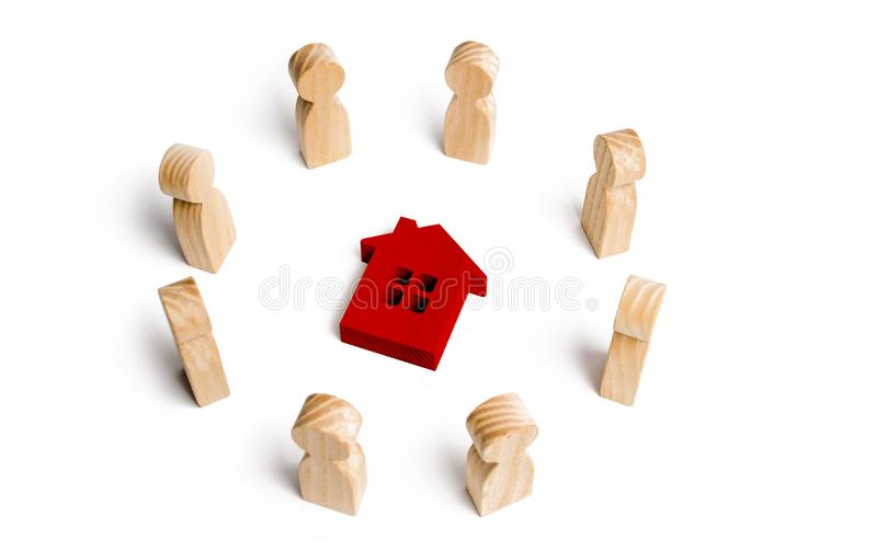 Wooden figurines of people stand around the house. Search for a new home and real estate. Buying or selling a home. Moving to a. New home. Rent or construction royalty free stock photos
