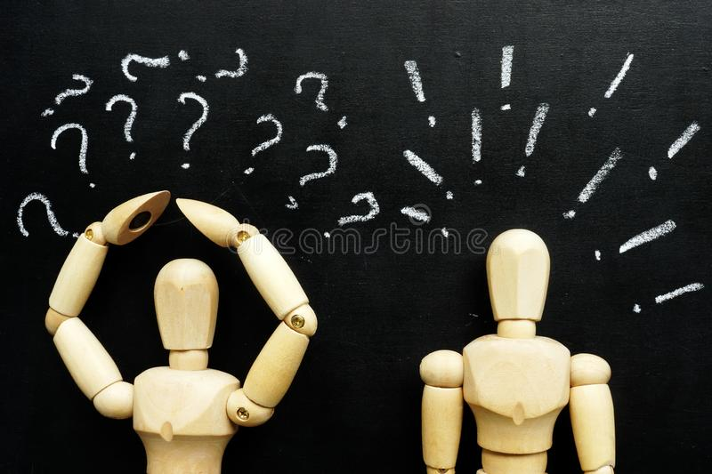 Figurines question and exclamation marks as symbols of difficulties in communication. Wooden figurines question and exclamation marks as symbols of difficulties stock photo