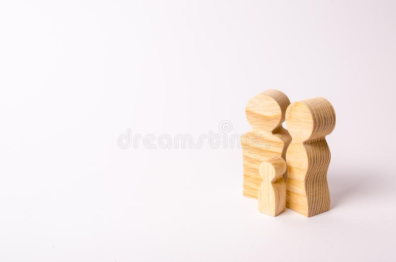 Wooden figurines of a young family on a white background. Concept of a young strong and healthy married couple. stock photos