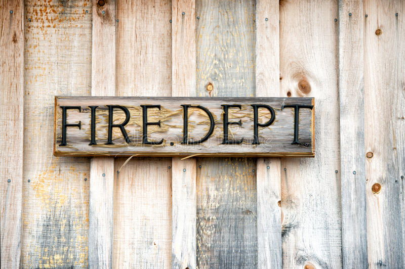 Wooden Fire Department Sign. A close up of the letters Fire Dept on an old weathered wooden sign board attached to the wooden siding of a building stock photo