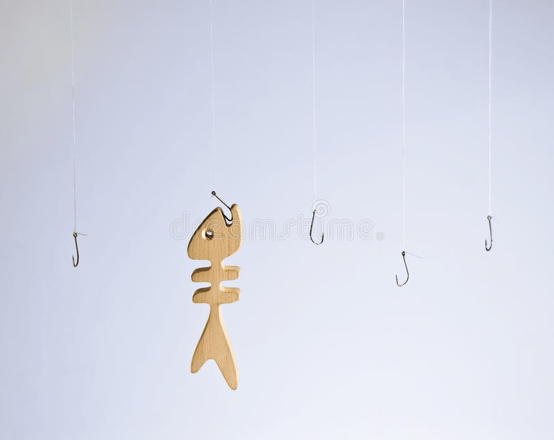 Wooden fish caught on hook royalty free stock photo