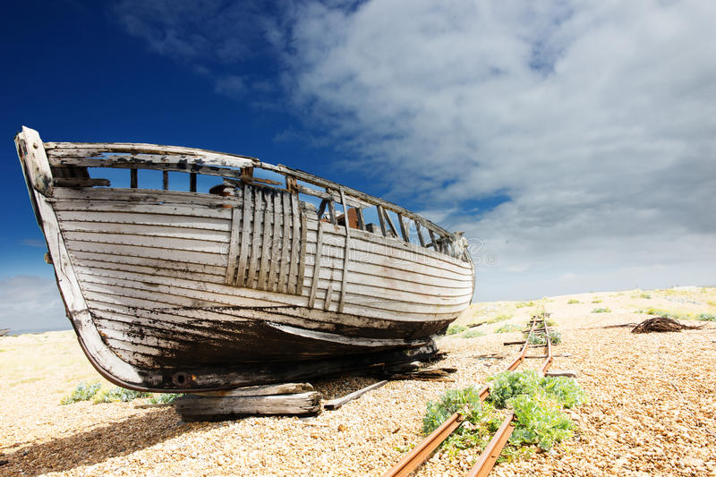 Wooden fishing boat left to rot and decay on the shingle beach at Dungeness, England, UK. Color image of an old wooden fishing boat left to rot and decay on the royalty free stock photos