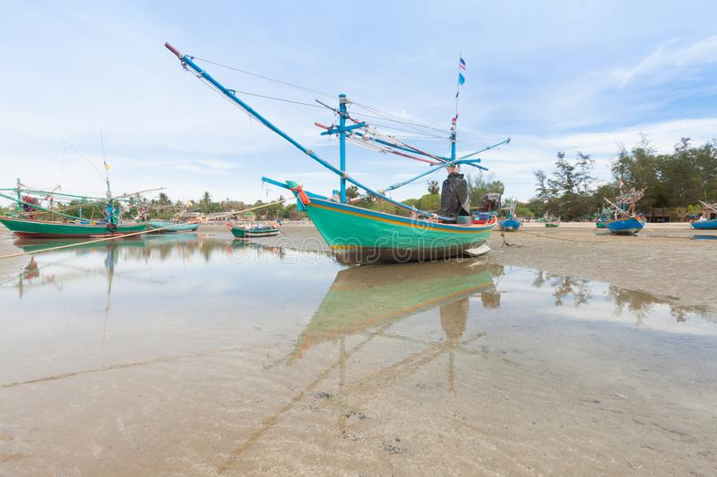 Wooden fishing boat on the low tide beach stock photography
