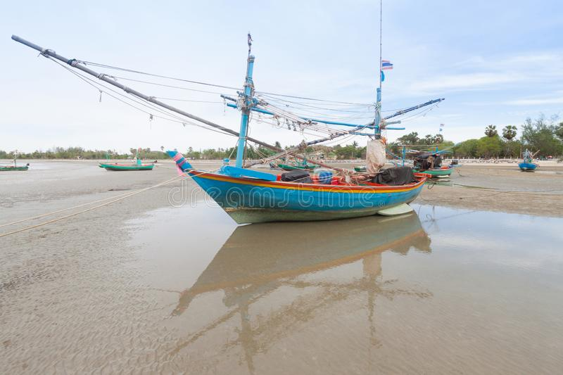 Wooden fishing boat on the low tide beach royalty free stock photo