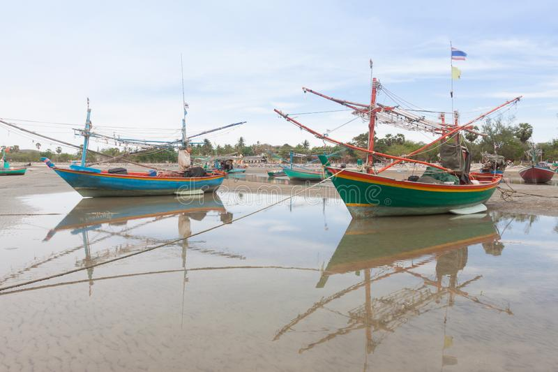 Wooden fishing boat on the  low tide beach royalty free stock photos