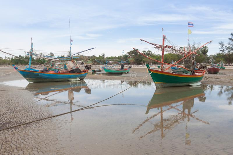 Wooden fishing boat on the  low tide beach stock image