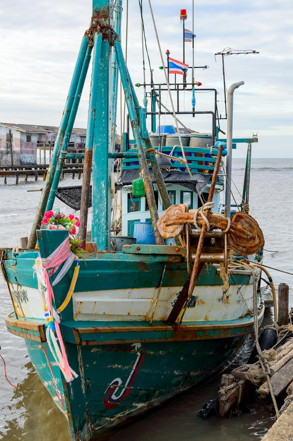 A wooden fishing boat moored to a pier in to the village stock photos