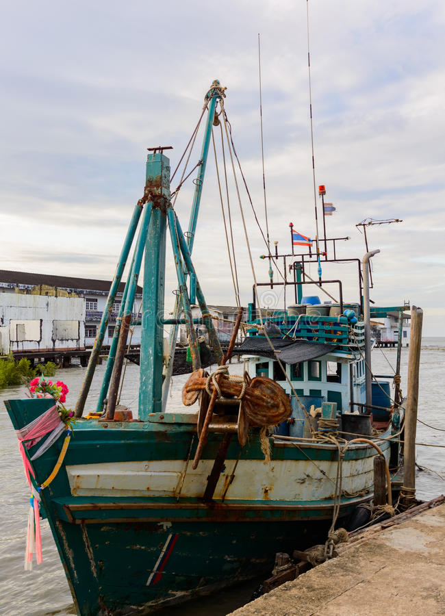 A wooden fishing boat moored to a pier in to the village stock images