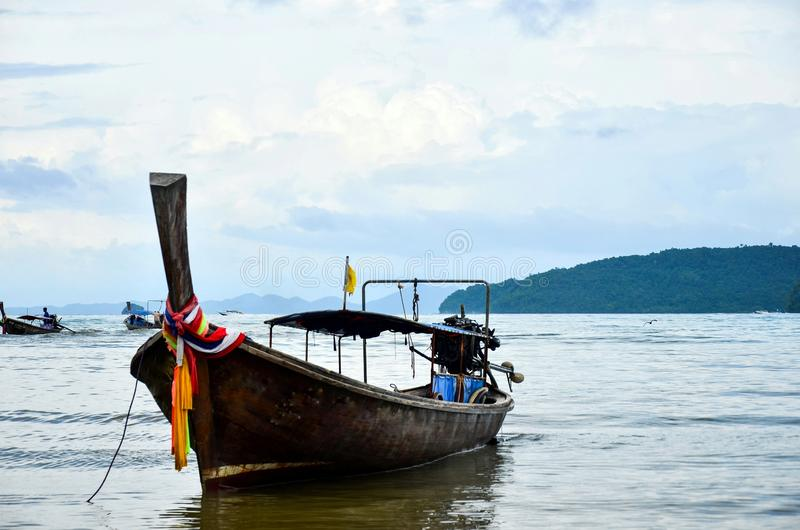 Wooden fishing boat on sea coast of tropical island in Thailand at sunny day of summer vacations in Asia stock photography