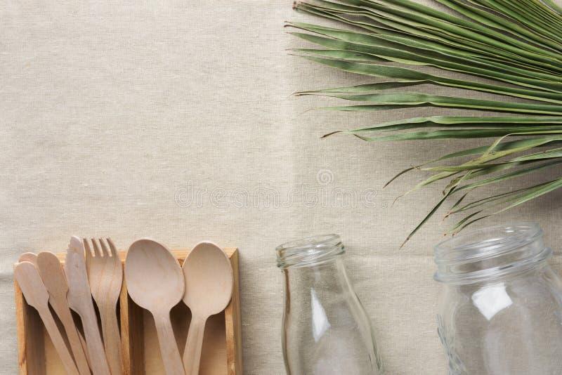 Wooden flatware cutlery crystal jar bottle green palm leaf on linen fabric background. Plastic-free alternatives zero waste royalty free stock photo
