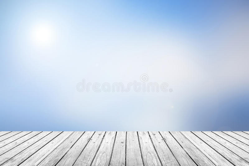 Wooden floor with blue sky blurred background. Gray (Grey) wooden floor with abstract blurred background in sky blue tone color. use for backdrop or web design stock photos