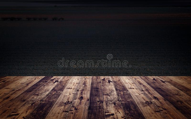 Wooden floor in front of a dark open country field image. royalty free stock photos
